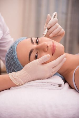 specialized: Side-view portrait of a young woman with fresh and clean skin looking at the camera lying on a table in healthy beauty spa salon getting a professional cosmetology skin care with specialized equipment