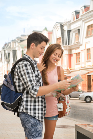 where to go: Waist-up portrait of a beautiful couple of tourists holding a map in their hands and funny laughing  and hugging each other while deciding where to go, concept of summer holidays and tourism Stock Photo