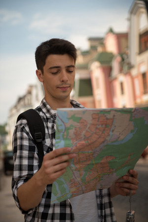 disoriented: Waist-up portrait of handsome male traveler on the street holding a map in his hands and looking at the map while calmly thinking where to go, concept of summer holidays and tourism  Stock Photo