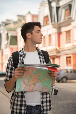 waistup: Retrato Waist-up de viajero de hombre guapo en la calle con un mapa en la mano y mirando a un lado mientras que con calma pensando a d�nde ir, el concepto de vacaciones de verano y el turismo