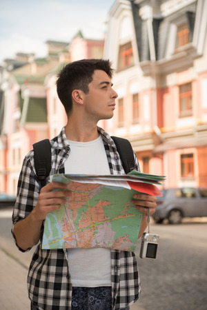 waistup: Waist-up portrait of handsome male traveler on the street holding a map in his hands and looking aside while calmly thinking where to go, concept of summer holidays and tourism