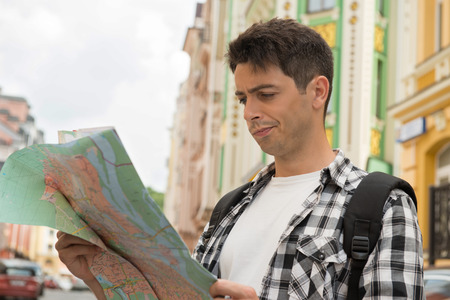 waistup: Waist-up portrait of dissatisfied handsome male traveler on the street holding a map in his hands and looking at the map while thinking where to go with irritation, concept of summer holidays and tourism Stock Photo