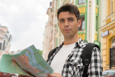 waistup: Retrato de la cintura en marcha de viajero insatisfecho var�n hermoso en la calle con un mapa en la mano y mirando a un lado mientras que el pensamiento de ensue�o d�nde ir, el concepto de vacaciones de verano y el turismo