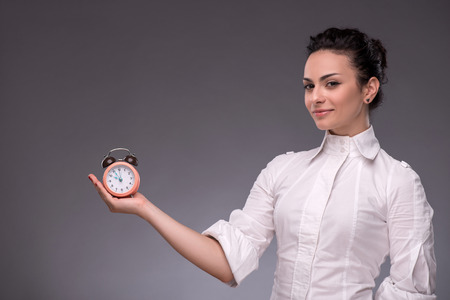 Close-up portrait of pretty girl with surprised face holding an alarm clock in her hand and calmly looking at the camera with a smile, with copy place isolated on grey background photo