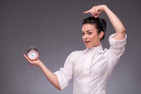 waistup: Retrato Cintura-para arriba de la muchacha bonita con la cara sorprendida que sostiene un reloj de alarma en su mano feliz mirando a la c�mara mostrando con el dedo a un reloj, con el lugar de copia aislada sobre fondo gris Foto de archivo