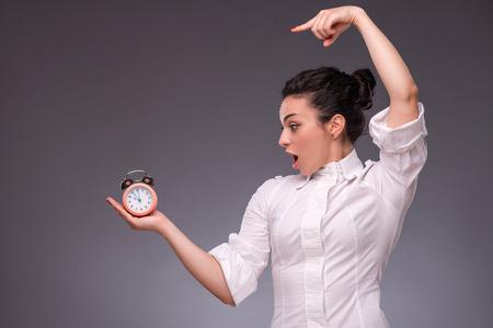 waistup: Retrato Cintura-para arriba de la muchacha bonita con la cara sorprendida que sostiene un reloj de alarma en su mano y mir�ndolo con la boca abierta mostrando con el dedo a un reloj, con el lugar de copia aislada sobre fondo gris