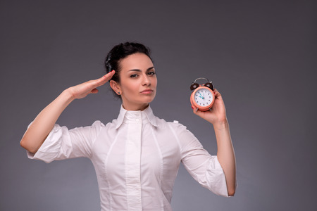 waistup: Waist-up portrait of beautiful girl looking at you while holding an alarm clock in her hand and saluting with her other hand, with copy place isolated on grey background Stock Photo