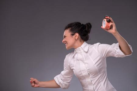 waistup: Retrato de la cintura de la muchacha enojada mirando a un lado mientras sostiene un reloj de alarma en su mano y quiere romperlo porque no tiene tiempo, con copia lugar aislado en el fondo gris Foto de archivo