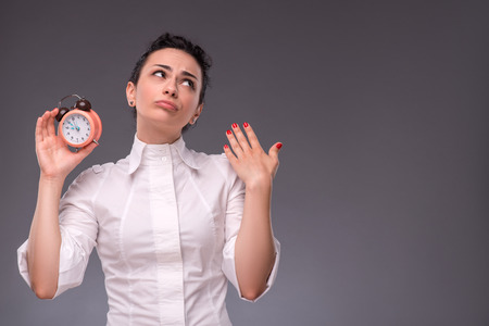 waistup: Retrato de la cintura-up de la hermosa ni�a de pensar en algo mientras sostiene un reloj de alarma en sus manos y mirando hacia arriba, con el lugar de la copia aislado en gris Fondo de concepto de gesti�n del tiempo