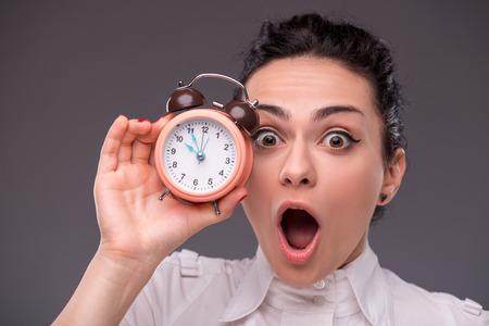 gestion del tiempo: Close-up retrato de la hermosa ni�a sorprendi� mirando y sosteniendo un reloj despertador en la mano, con el lugar de la copia aislado en gris Fondo de concepto de gesti�n del tiempo Foto de archivo
