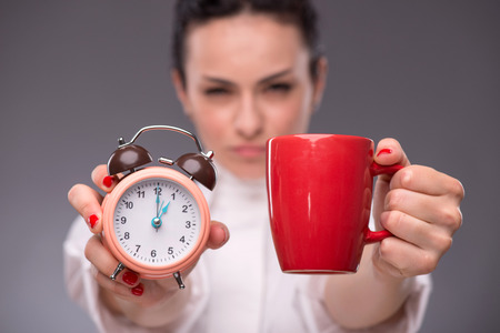 coffeebreak: Close-up picture with selective focus alarm clock and a red cup in hands of young woman isolated on grey background concept of time management and coffee-break
