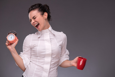 coffeebreak: Waist- up portrait of happy girl holding an alarm clock and a red cup in her hand with closed eyes isolated on grey background with copy place concept of time management and coffee-break