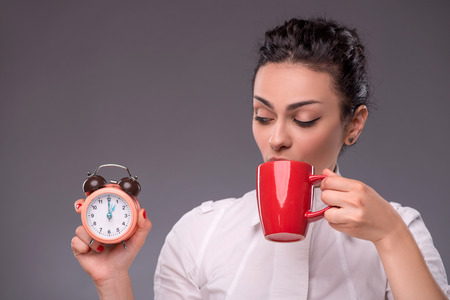 coffeebreak: Waist- up portrait of happy girl holding an alarm clock in her hand and drinking from a red cup isolated on grey background with copy place concept of time management and coffee-break