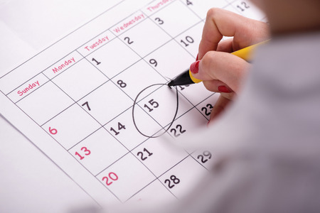 Close-up top-view photo of calendar with a datum circled by young woman with red nails photo