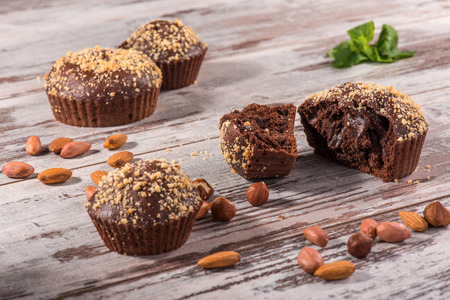 Close-up picture of four chocolate cupcakes one of them broken decorated with almonds, hazelnut and mint on wooden table in cafe with copy place photo