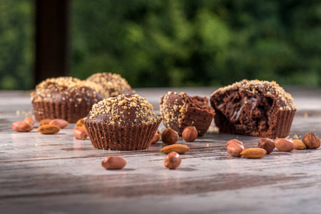 Close-up picture of four chocolate cupcakes one of them broken decorated with almonds and hazelnut on wooden table in cafe with selective focus only on two of the cupcakes with copy place photo