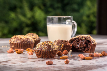 Close-up picture cup of milk and four chocolate cupcakes one of them broken decorated with almonds and hazelnut on wooden table in cafe with copy place photo