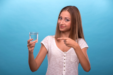 Waist-up portrait of young beautiful girl smiling looking at the camera while holding a glass with clean water showing with her finger on a glass isolated on blue background with copy place photo