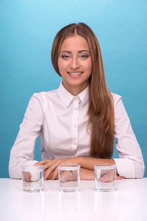 waistup: Retrato Waist-up de la hermosa joven vestido con camisa blanca que mira a la c�mara con una sonrisa sincera mientras estaba sentado en la mesa cerca de tres vasos con agua limpia aisladas sobre fondo azul con copia lugar Foto de archivo