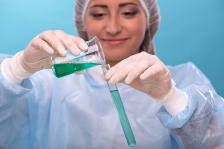waistup: Waist-up portrait of happy female scientist smiling in overall while pouring some green substance from a flask to a tube in laboratory and doing some experiments isolated on blue background Stock Photo