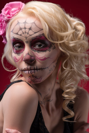 Close-up portrait of young blond girl with sad face with Calaveras makeup and a rose flower in her hair upset looking at the camera isolated on red background photo