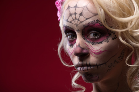 Close-up portrait of young blond girl with sad face with Calaveras makeup and a rose flower in her hair upset looking at the camera isolated on red background with copy place photo