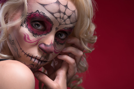 Close-up portrait of young blond girl with sad face with Calaveras makeup upset looking at the camera while holding her hands near face isolated on red background with copy place photo