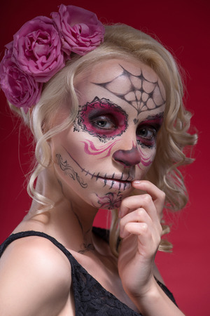 Close-up portrait of young blond girl with sad face with Calaveras makeup and a rose flower in her hair upset looking at the camera while holding her hand near face isolated on pink background photo