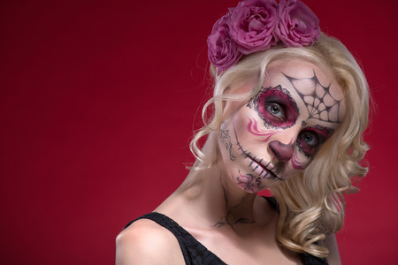 Close-up portrait of young blond girl with sad face with Calaveras makeup and a rose flower in her hair curiously looking at the camera isolated on red background with copy place photo