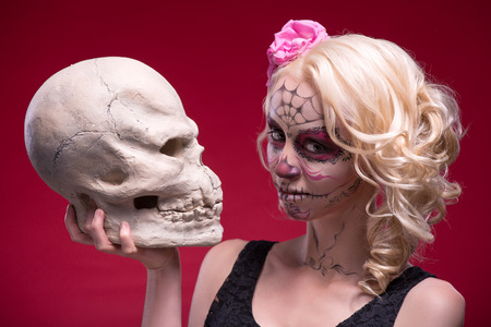 Close-up portrait of young blond girl with sad face with Calaveras makeup and a rose flower in her hair curiously looking at the camera while holding a skull isolated on red background with copy place photo
