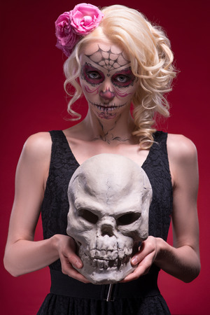 Close-up portrait of young blond girl with sad face with Calaveras makeup and a rose flower in her hair seriously looking at the camera while holding a skull isolated on red background photo