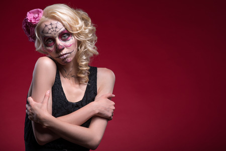 Waist-up portrait of young blond girl with sad face with Calaveras makeup and a rose flower in her hair hopefully looking at the camera and hugging herself isolated on red background with copy place photo