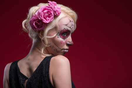 Close-up portrait of young blond girl with sad face with Calaveras makeup and three rose flowers in her hair looking aside with a fright isolated on red background with copy place photo