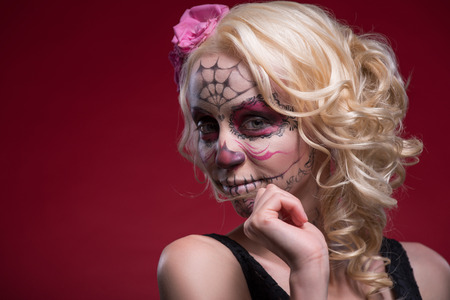 Close-up portrait of young blond girl with lightly smiling face with Calaveras makeup and a rose flower in her hair looking confident at the camera isolated on red background with copy place photo