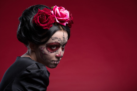 Close-up portrait of young girl in black dress with Calaveras makeup and a red flower in her black hair looking aside isolated on red background with copy place photo
