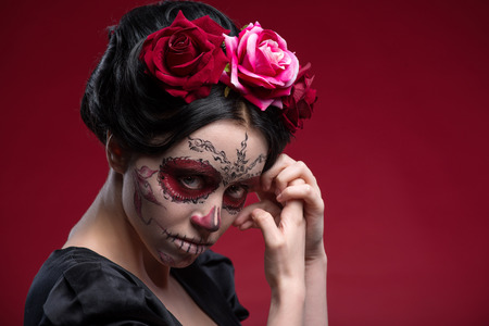 Close-up portrait of girl with Calaveras makeup and a red flower in her black hair looking at you under a forehead and holding her hands near her face isolated on red background with copy place photo
