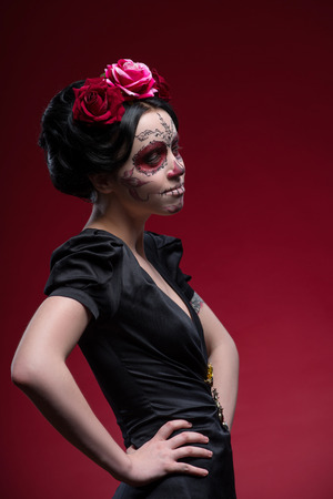 Waist-up portrait of young girl in black dress with Calaveras makeup and a red flower in her black hair looking aside isolated on red background photo