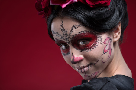 Close-up portrait of girl with Calaveras makeup and a red flower in her black hair looking at you and lightly smiling isolated on red background with copy place photo