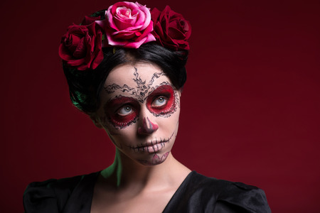 Close-up portrait of girl with Calaveras makeup and three red flowers in her black hair seriously looking aside isolated on red background with copy place photo