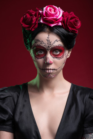Close-up portrait of girl with Calaveras makeup and a red flower in her black hair frustrated looking at you isolated on red background with copy place photo