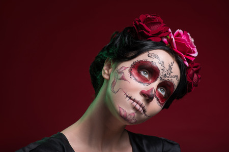 Close-up portrait of girl with Calaveras makeup and three red flowers in her black hair looking aside with a light smile and thinking about something isolated on red background with copy place photo