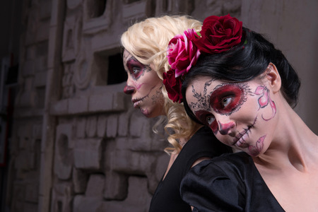 scheming: Close-up portrait of two young girls in black dresses with Calaveras makeup and roses in their hair looking aside while scheming something in ancient temple interior