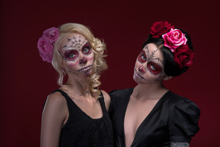 Waist-up portrait of two young girls standing near each other in black dresses with Calaveras makeup and roses in their hair looking at the camera isolated on red background with copy place Stock Photo