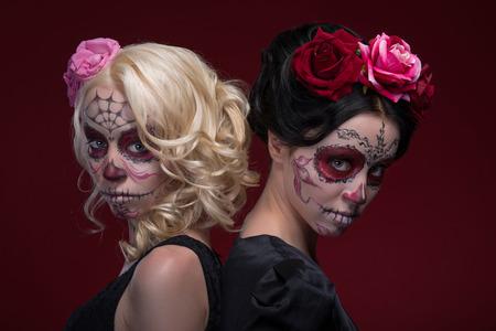 trajes mexicanos: Retrato Cintura-para arriba de dos chicas jóvenes de pie espalda con espalda en vestidos negros con Calaveras maquillaje y rosas en su pelo extrañamente mirando a la cámara aislada en fondo rojo con copia lugar Foto de archivo