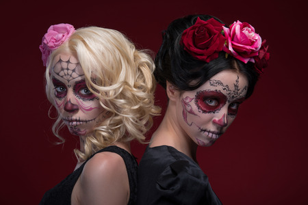 waistup: Waist-up portrait of two young girls standing back to back in black dresses with Calaveras makeup and roses in their hair eerily looking at the camera isolated on red background with copy place