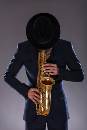 Full-length portrait of a jazz man in a suit with a black hat lowered his head down hiding his face and playing a trumpet isolated on grey background with copy place, concept of jazz music