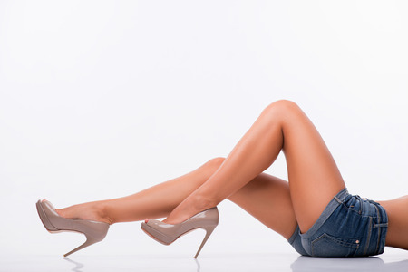 feet naked: Half-length portrait of woman wearing blue shorts having perfect legs wearing grey high heels lying showing us her beauty isolated on white background