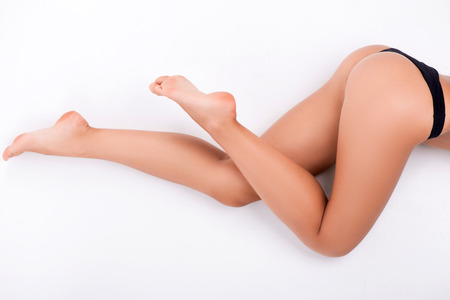 feet naked: Half-length portrait of sexy woman wearing black lingerie lying aside demonstrating us her perfect figure isolated on white background