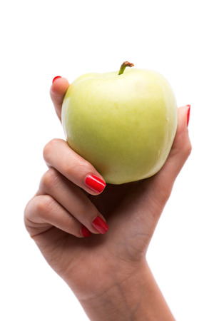 hardships: Woman with nice red polished nails holding ripe green apple. Isolated on white background