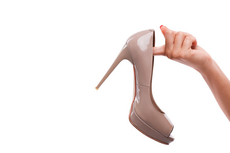 hardships: Woman with nice red polished nails holding one high heel in her hands. Isolated on white background Stock Photo